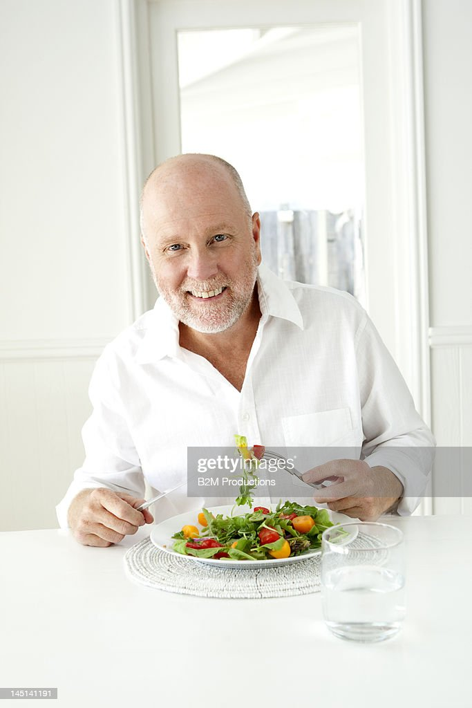 Happy mature man eating a salad : Stock Photo