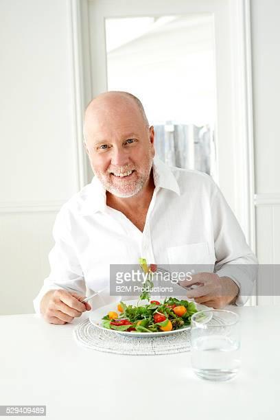 Happy mature man eating salad