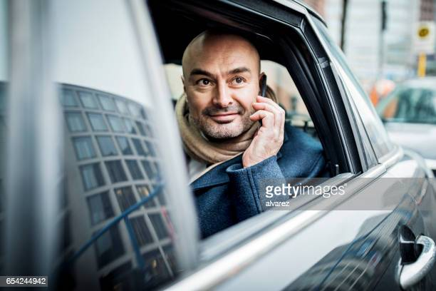 Happy mature man in the car talking on mobile phone