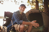 Portrait of a happy mature man sitting in front of a tent and looking at camera. Senior caucasian man at campsite.