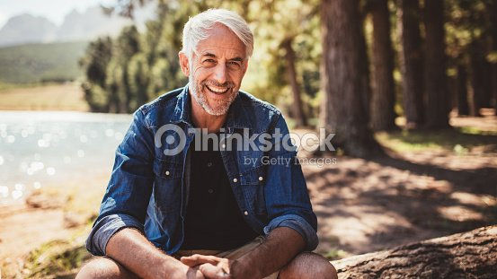 Happy mature man sitting near a lake : Stock Photo