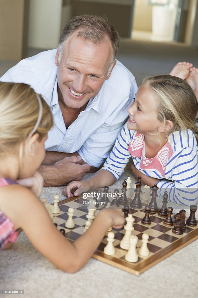 Happy mature man watching kids play chess at home : Stock Photo