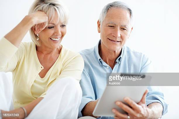 Happy mature man with a woman holding touchpad against white