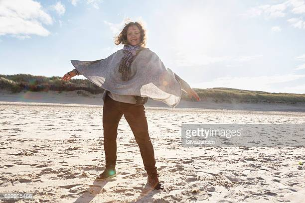 happy mature woman arms outstretched at beach in winter