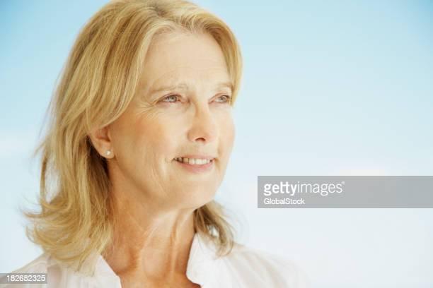 Heureuse femme mature regardant loin de réflexion