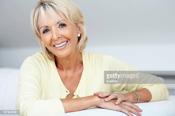 Heureuse femme d'âge mûr souriant se détendre dans le canapé-lit