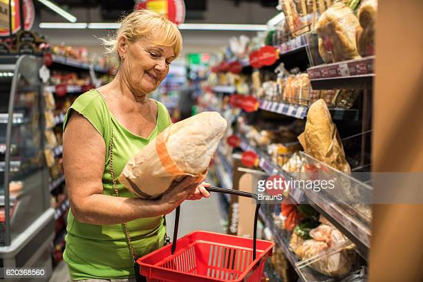 Happy mature woman shopping for bread in a store.