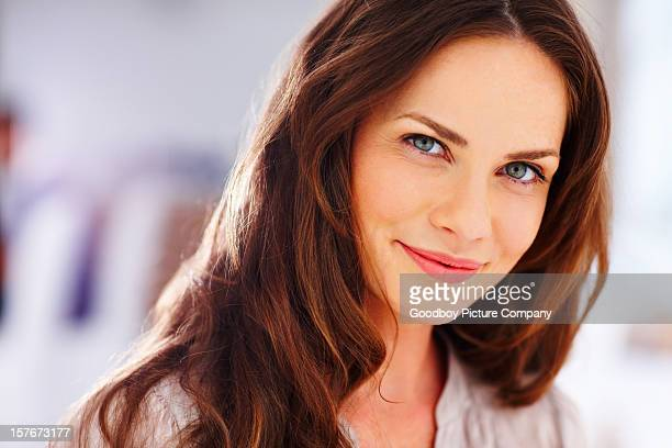 Happy mature woman smiling against blur background