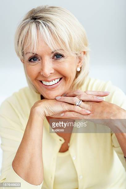 Happy mature woman smiling with hands on chin