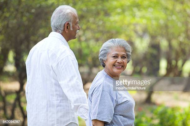 Happy mature woman smiling with man while walking in park