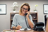 Beautiful mature woman talking on phone at creative office. Happy smiling businesswoman answering telephone at office desk. Casual business woman sitting at her desk making telephone call and taking n