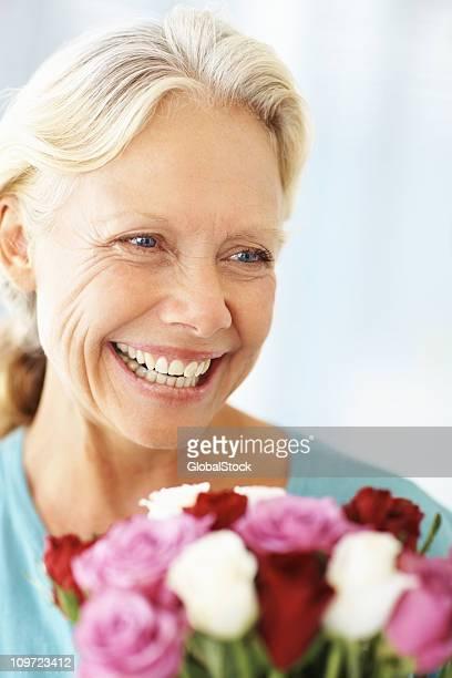 Heureuse femme mature avec un bouquet de roses