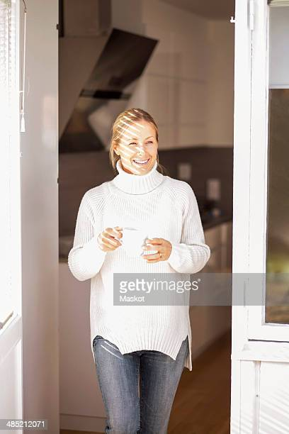 Happy mature woman with coffee cup leaving house