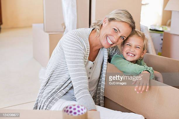 Happy mature woman with her daughter unpacking cardboard boxes at new house