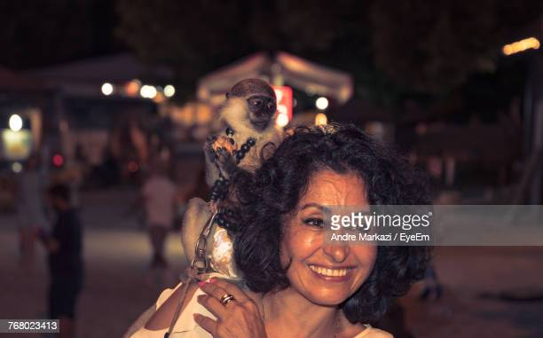 Happy Mature Woman With Monkey On Shoulder At Night