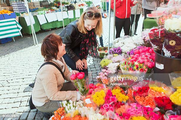 Happy mature women buying flowers at market stall