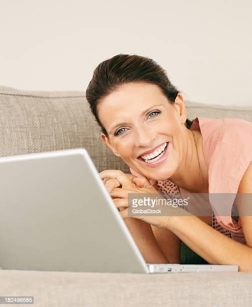 maturewoman heureuse avec un ordinateur portable, allongé sur le canapé à la maison
