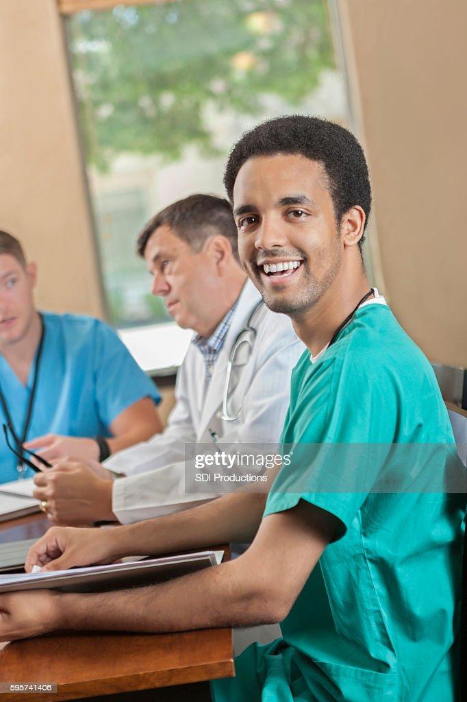 Happy medical intern attending hospital staff meeting