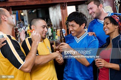 Happy men shaking hands in sports bar