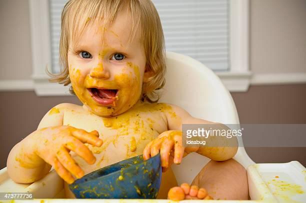 Glücklich schmutzig Baby Essen im Hochstuhl