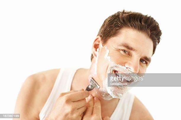 Happy mid adult guy shaving with razor