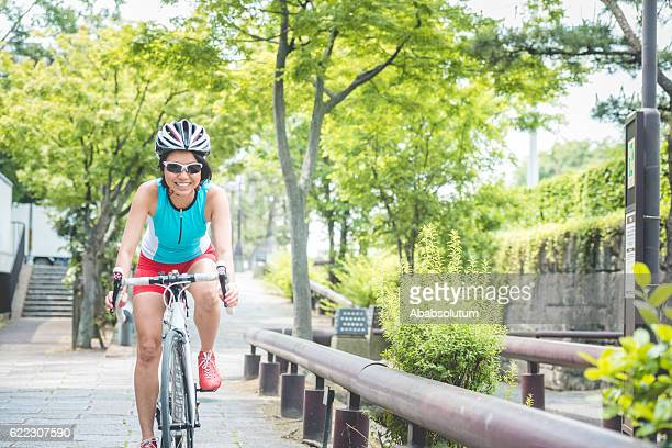 Happy Mid Adult Japanese Woman Riding Bike in Kyoto, Japan