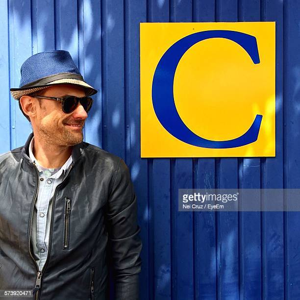 Happy Mid Adult Man Standing By Letter On Blue Wall