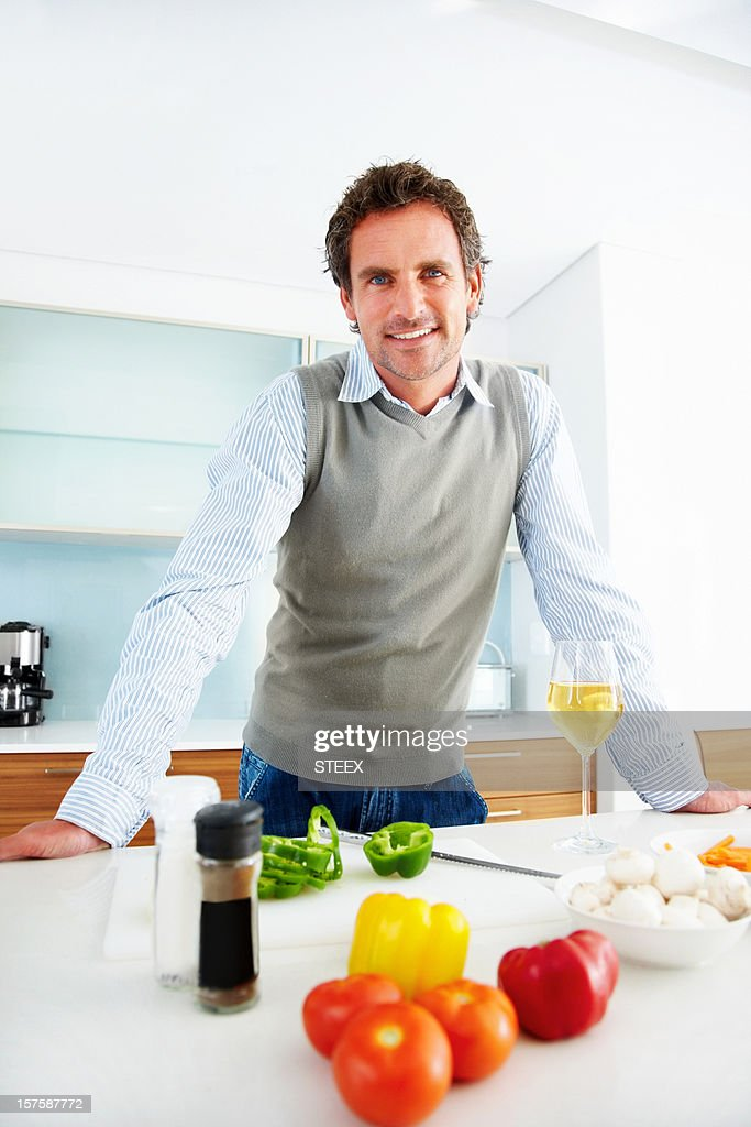 Happy mid adult man standing in kitchen : Stock Photo