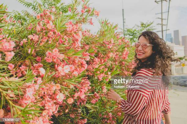 Happy mid adult woman standing by pink flowers on sunny day, Los Angeles, California, USA
