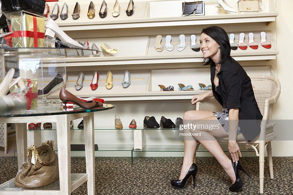 Happy mid adult woman trying high heels in footwear store