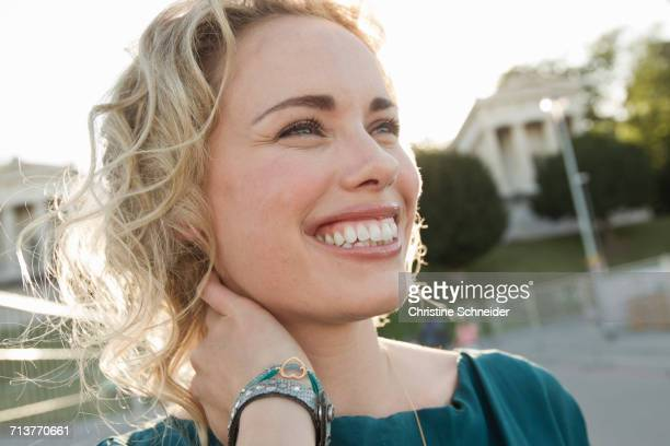 Happy mid adult woman with hand on neck in park