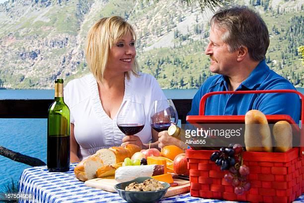 Happy middle age couple enjoying picnic by lake