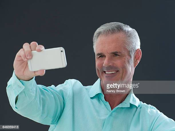 Happy Middle Age Man Taking Selfie with Smart Ph.