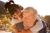 Happy middle aged couple piggybacking on the beach, Ibiza