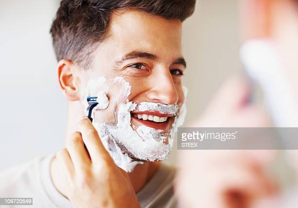 Happy middle aged man using razor to shave