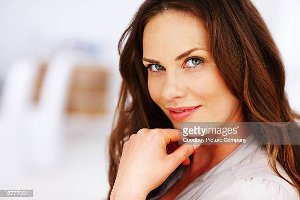 Happy middle aged woman with hand on chin