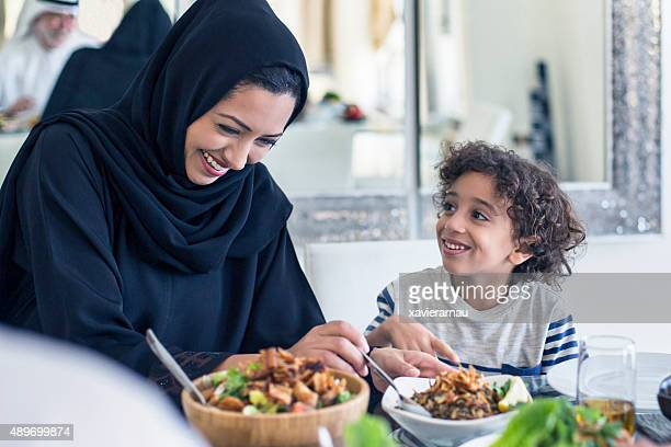 Happy middle Eastern mother and son having lunch
