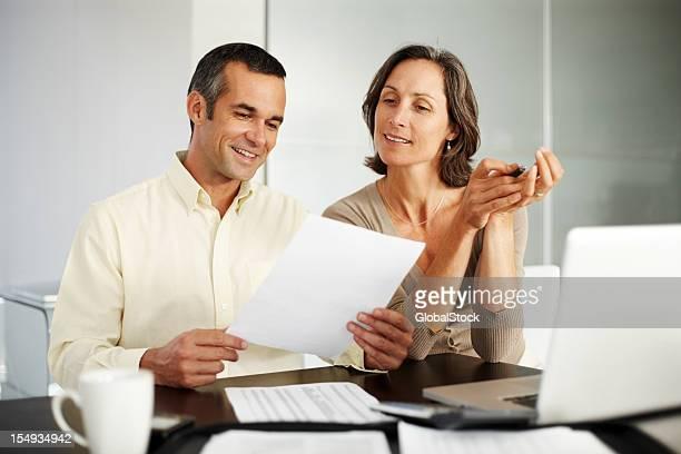Heureux couple âgé moyen, travaillant sur les dépenses financier