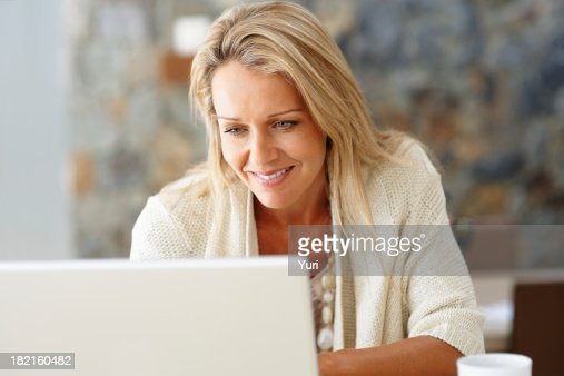 'Happy, middle-aged woman using a laptop'