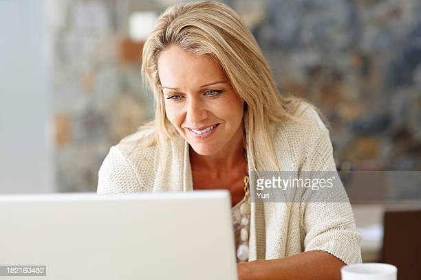 Happy, middle-aged woman using a laptop