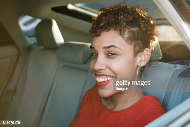 Happy Millennial American Woman Rideshare Passenger Smiling in Car's Backseat