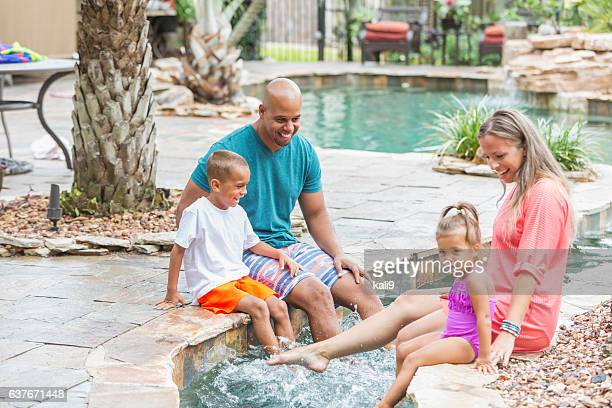 Happy mixed race family at resort swimming pool