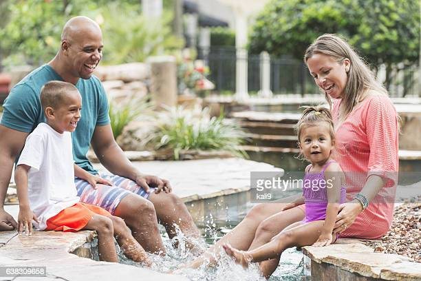Happy mixed race family at resort swimming pool, waving