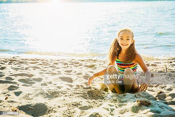 Happy mixed race girl playing in sand by lake