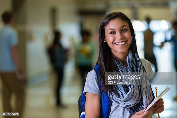 Happy mixed race teen girl in high school hallway