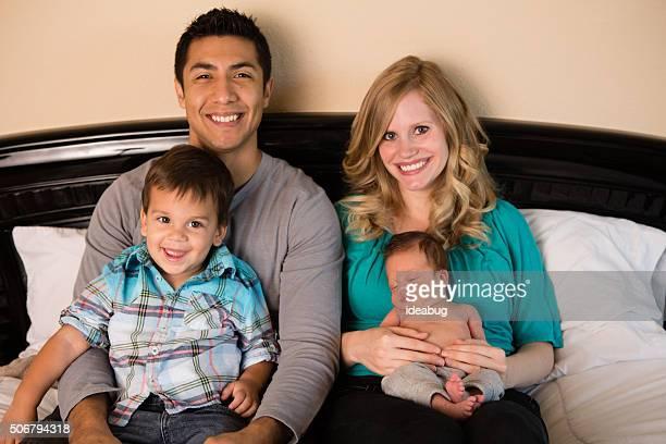 Famille heureuse Race mixte assis sur le lit ensemble