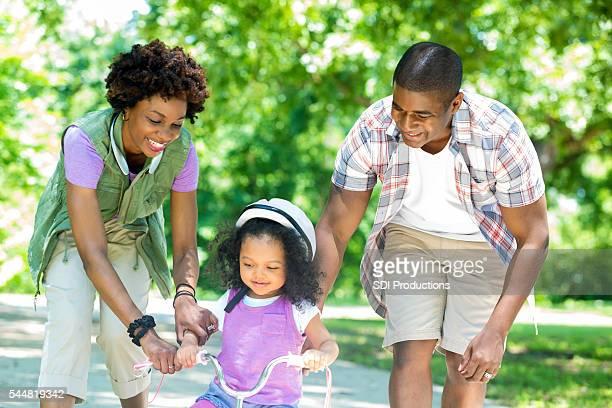 Glückliche Mutter und Vater Lehre Tochter Reiten Dreirad