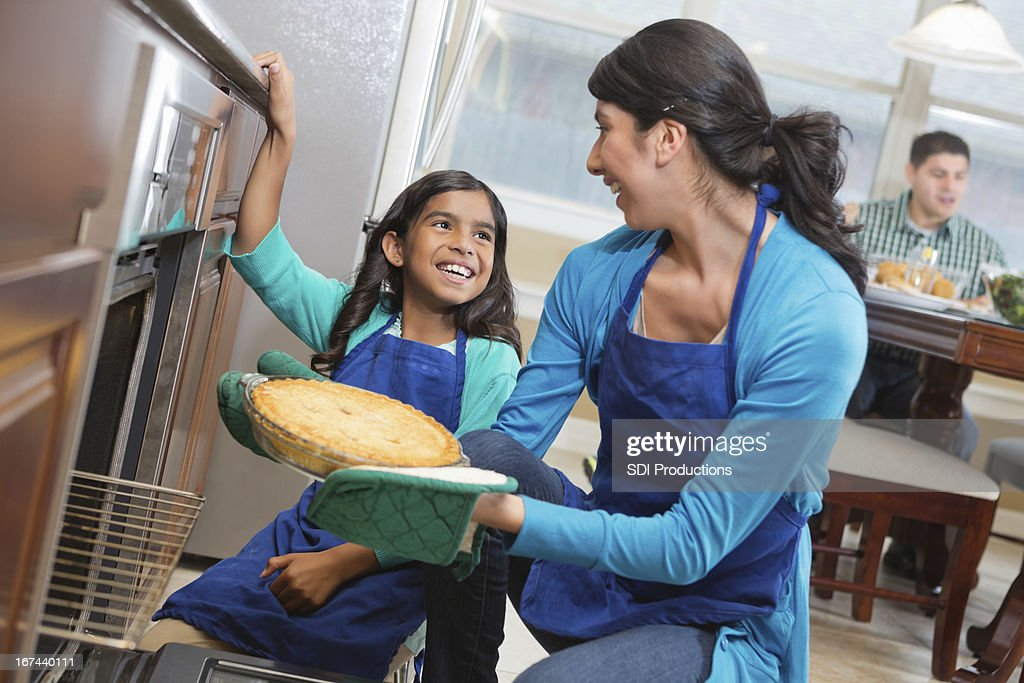 Happy mom and daughter baking together in modern kitchen : Stock Photo
