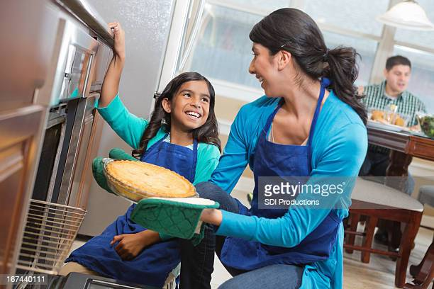 Happy mom and daughter baking together in modern kitchen