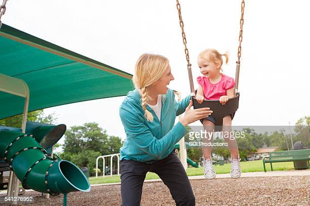 Happy mom and daughter play on the swing at playground